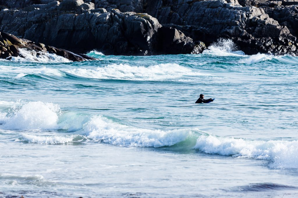 En surfer venter på de rette bølgene på Sandvesand