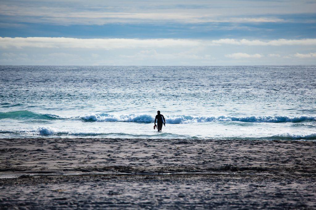 En surfer er på vei opp av vannet på Sandvesand