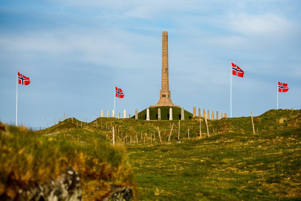 Haraldshaugen og fire norske flagg som vaier i vinden