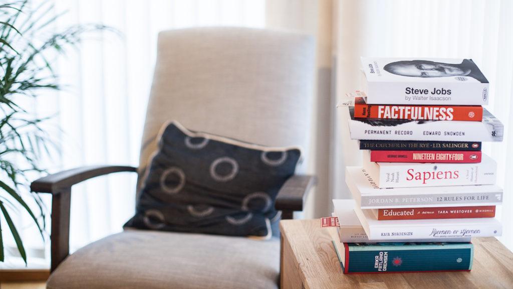 En lesestol og et bord med en stabel av bøker.