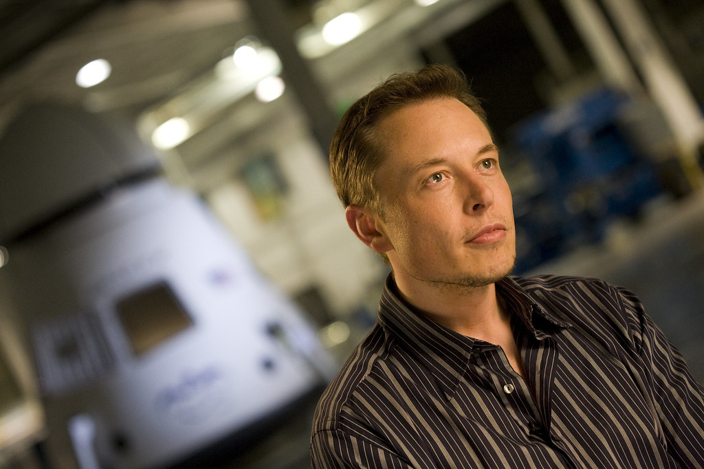 Elon Musk in front of a SpaceX Dragon capsule